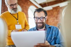 Economists working. One of contemporary economists reading document while his mature colleague standing near by stock image
