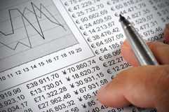 Economy. Man's hand holding a pen on top of a document with numbers and a chart Stock Image