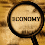 Economy. On a grunge background with a magnifier Royalty Free Stock Photos
