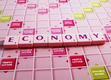 Economy. The word economy spelled out in letters on a board - pink tiles with green and pink board royalty free stock photo