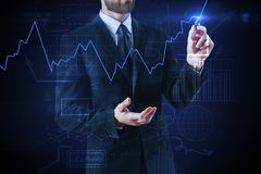 Economy and banking concept. Unrecognizable businessman drawing glowing forex chart on dark blue background. Economy and banking concept. Double exposure Stock Photo