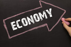 Economy - Chalkboard with arrow on black Stock Images