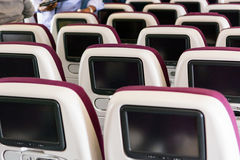 Economy class airplane interior. LCD displays on the rear side of seats Stock Images