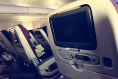 Economy class airplane interior. LCD displays on the rear side of seats Royalty Free Stock Photos