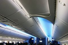 Economy Class cabin, American Airlines Boeing 787. Economy class cabin in an American Airlines Boeing 787 Dreamliner, with cool coloured cabin ambience stock photography