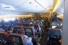 Economy Class cabin, Japan Airlines Boeing 777. Economy class passengers in a Japan Airlines JAL Boeing 777 with 3-3-3 seat configuration, and warm coloured stock image
