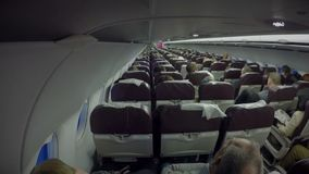 Economy class passengers sitting inside plane cabin. Air transport services