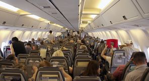 Economy class passengers take their seats and get ready for the takeoff in the cabin of a Boeing 767 - 300 airplane stock image