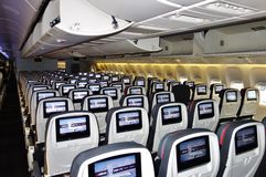 Economy class seats on an Air Canada Boeing 777. TORONTO, CANADA -Rows of tightly packed seats in an Economy cabin inside a Boeing 777 from Air Canada (AC Stock Images
