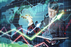 Economy concept. Handsome businessman with notepad on forex chart background. Economy concept Royalty Free Stock Image