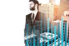 Economy concept. Handsome young businessman standing on city background with business chart bars and copy space. Economy concept. Double exposure stock photography