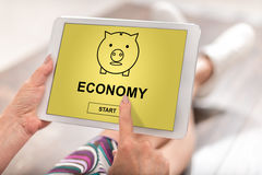 Economy concept on a tablet. Woman using a tablet with economy concept Royalty Free Stock Photos