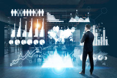 Economy concept. Thoughtful businessman in dark office analyzing digital business panel with charts and diagrams. Economy concept stock images