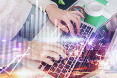 Economy concept. Young woman at office desk with coffee cup using laptop computer with forex trading business graph. Economy concept. City background. Double Royalty Free Stock Photo