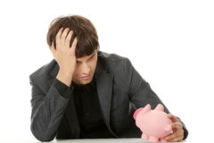 Economy crisis concept. Young depressed businessman holding piggy bank. Economy crisis concept Stock Photography