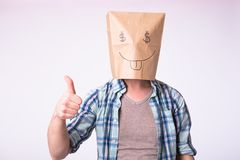 Economy, emotion, and money concept - Man with cardboard box on his head with picture of dollar symbol instead of eyes. stock photos