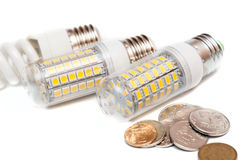 Economy of energy. Close-up LED Bulb isolated on white with money royalty free stock image