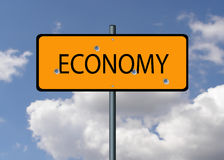Economy falling. Economy road sign with bullet holes in it Stock Images