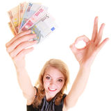 Economy finance. Woman holds euro currency money. Rich happy blonde business woman showing euro currency money banknotes, giving ok hand sign gesture. Economy stock photography