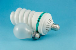 Economy lamp incandescent bulb on blue background Royalty Free Stock Image