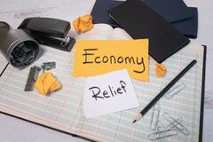Free Economy Relief Sign Laying On An Open Small Business Bookkeeping Financial Account Ledger Stock Photos - 180452063