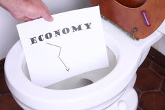 Economy In The toilet. Mans Hand holding a economy sign in a toilet Stock Photo