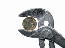 Economy under pressure. An euro coin in a gripper stock photos