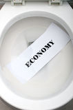 Economy in a white toilet Stock Images