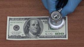 Econoom die met stethoscoop de gezondheid van het dollarbankbiljet kijken stock video
