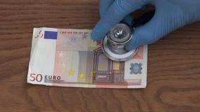 Econoom die met stethoscoop euro geldgezondheidsvoorschrift kijken stock footage