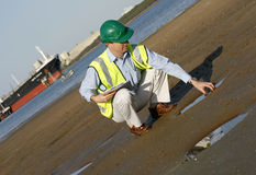 Ecosytem in trouble. An environmental engineer on the mudflats examining a sample of oil from the ship docked behind him, showing the estuary royalty free stock photo