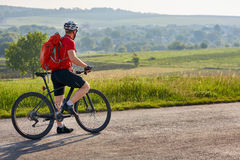 Ecotourism in Europe. Bicycle race in the country. Bicyclist traveler with backpack has adventure on european country road. Cyclist in white helmet and red t royalty free stock photography