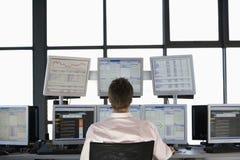 Ecrãs de computador de Looking At Multiple do comerciante conservado em estoque Imagem de Stock Royalty Free