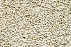 Ecru plaster from pebbles on wall closeup Stock Images