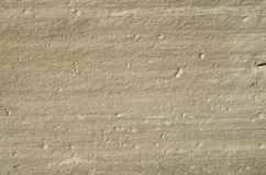 Ecru sandstone with grooves closeup. In sunny day Royalty Free Stock Image