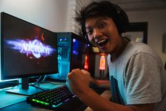 Ecstatic asian gamer boy rejoicing victory while playing video g. Ames on computer in dark room wearing headphones and using backlit colorful keyboard stock image