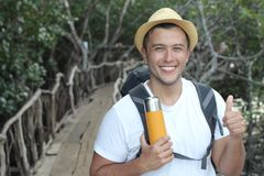 Ecstatic backpacker giving thumbs up from the jungle.  Stock Photo