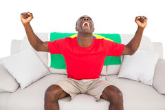 Ecstatic brazilian football fan sitting on couch cheering Stock Images