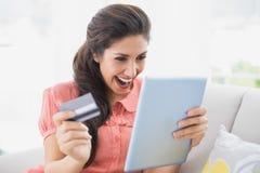 Ecstatic brunette sitting on her sofa using tablet to shop online stock images