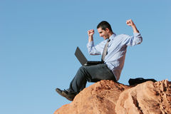 Ecstatic businessman. Working on his laptop royalty free stock photo