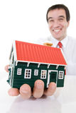 Ecstatic businessman with a miniature house Stock Image