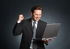 Ecstatic and enthusiastic businessman with laptop - good news, c Stock Image