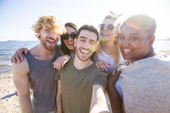 Restful friends. Ecstatic friends enjoying their rest on the beach and making selfie Royalty Free Stock Images