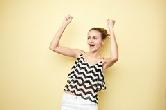 Ecstatic girl dressed in a striped top and white jeans happily shouts on the yellow background in the studio royalty free stock images