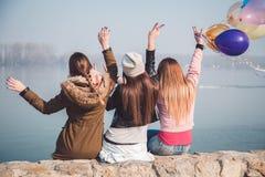 Ecstatic girls waving on river bank. Ecstatic girls waving happily on river bank Stock Photo
