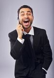 Ecstatic About a Good News!. Ecstatic businessman with a cell phone excited about a good news stock image