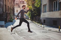 Ecstatic hipster jumps in the street with his mouth open stock photography