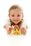 Ecstatic little girl with her clay house. Grimacing happily - isolated stock image