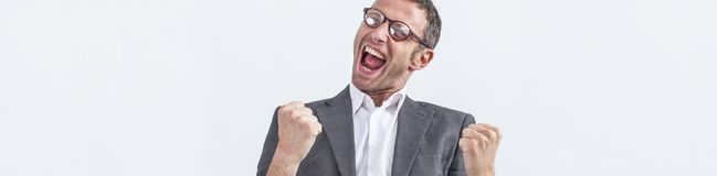 Ecstatic middle aged businessman screaming his victory, white long banner. Conviction concept - ecstatic middle aged businessman with dynamic body language Royalty Free Stock Images