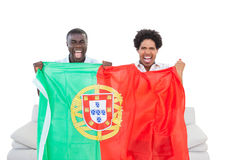 Ecstatic portugal fans sitting on the couch with flag Stock Photo